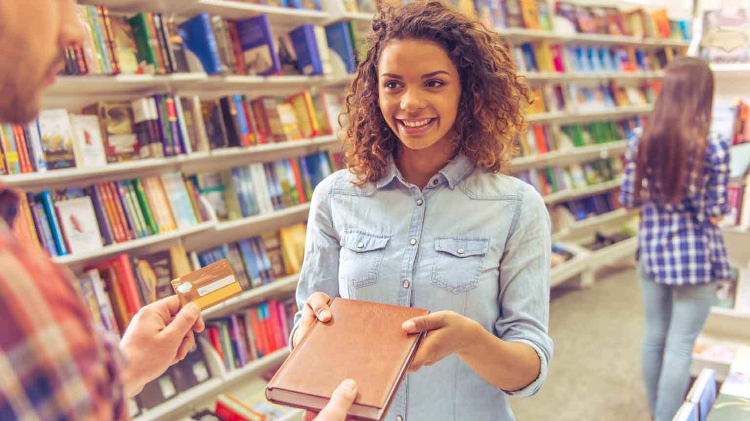 student buying book at the bookshop using a credit card