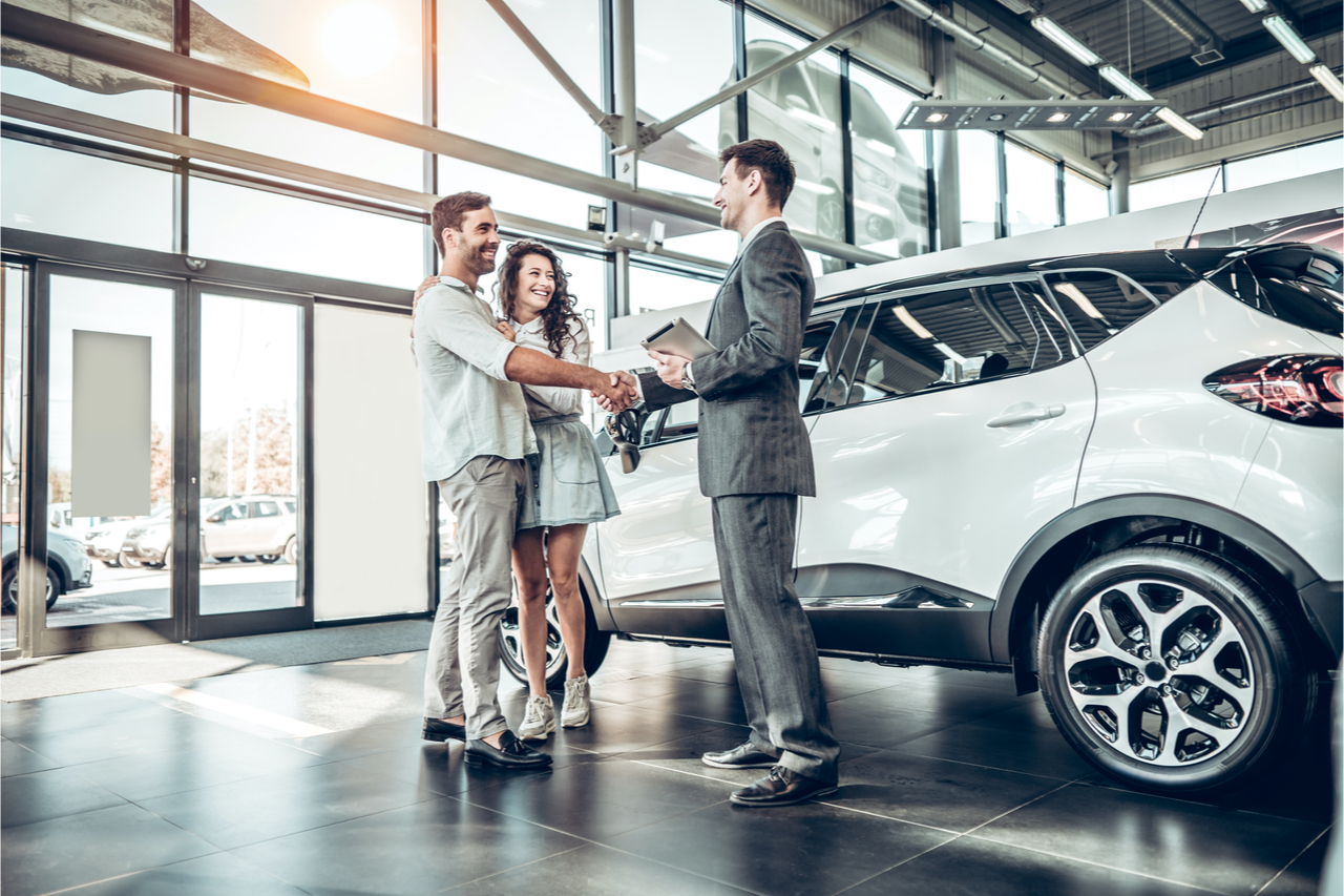 A couple purchasing a new car at a dealership