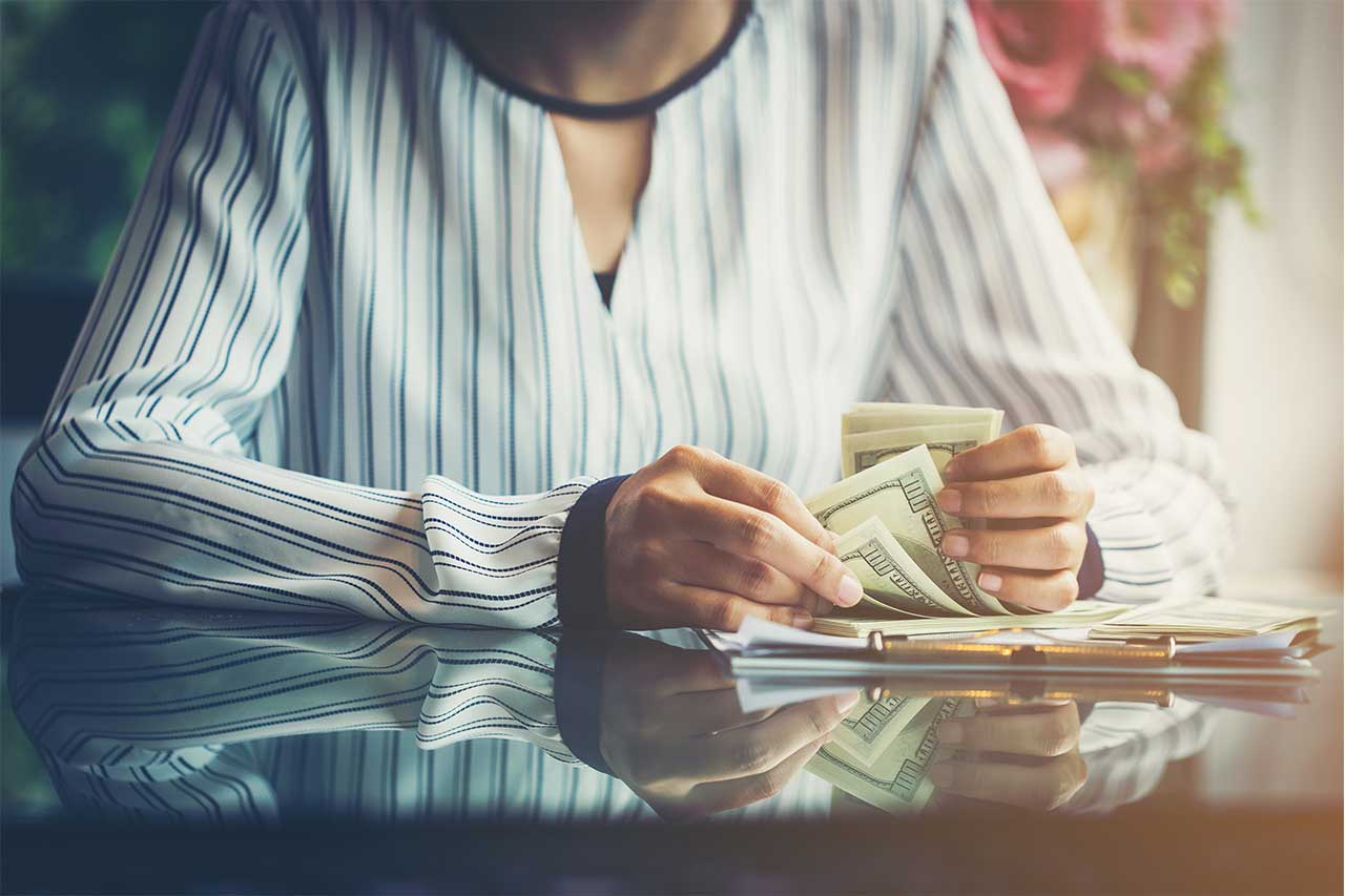Woman with money on desk